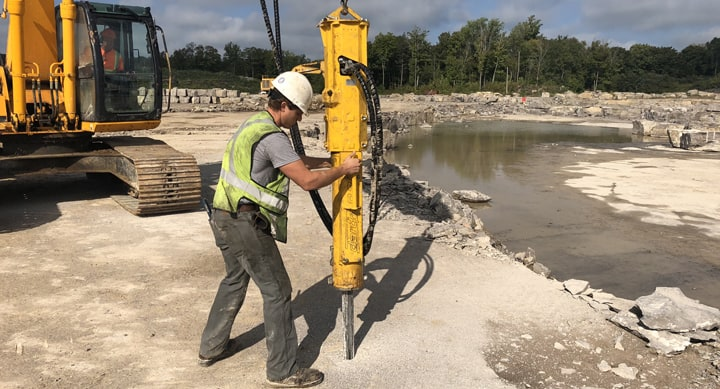 man using a darda rock splitter to break ground