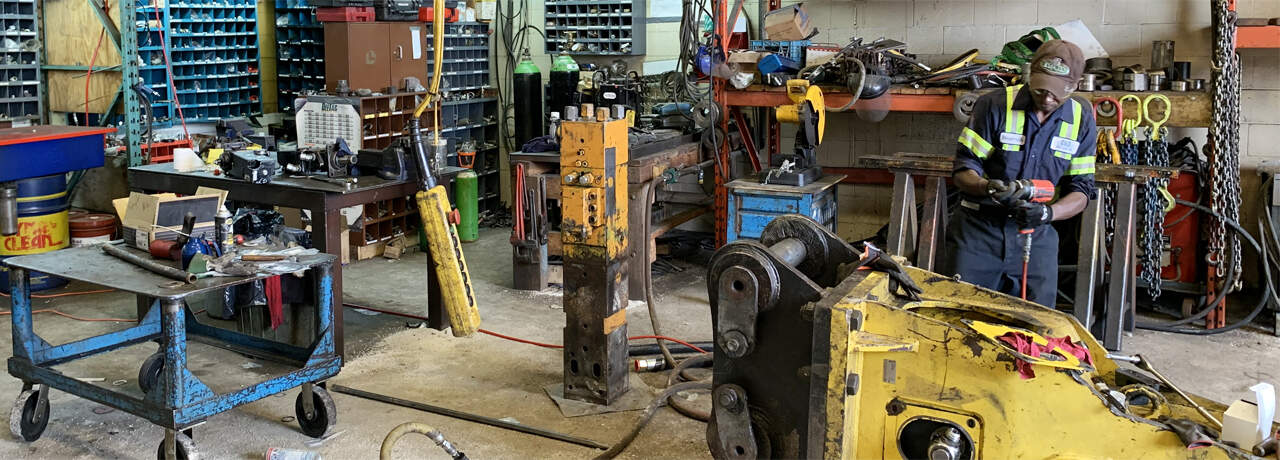 man working on construction equipment inside a garage